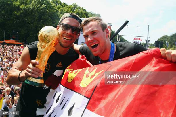 Lukas Podolski and Kevin Grosskreutz celebrate on stage at the German team victory ceremony on July 15 2014 in Berlin Germany Germany won the 2014...