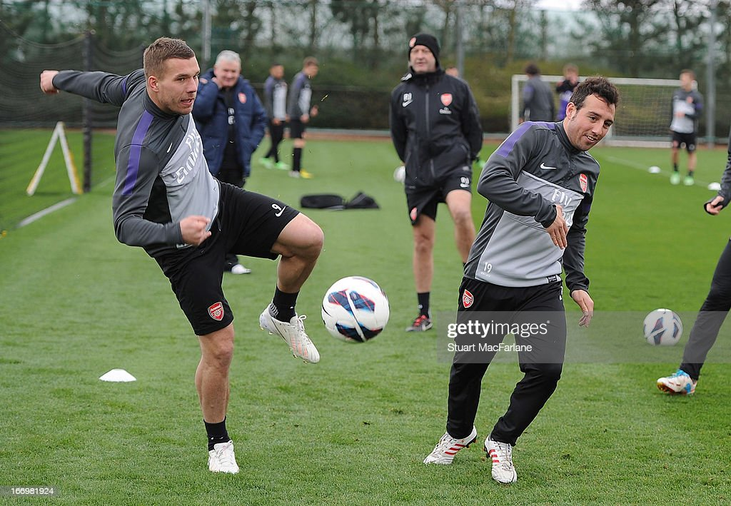 Lukas Podolski and Santi Cazorla of Arsenal during a training session at London Colney on April 19, 2013 in St Albans, England.