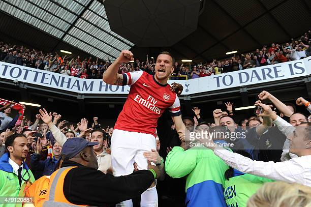 Lukas Podolski celebrates with the Arsenal fans after the Barclays Premier League match between Tottenham Hotspur and Arsenal at White Hart Lane on...