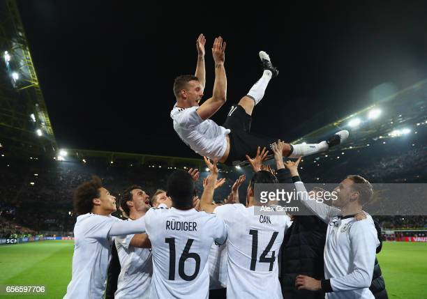 Lukas Podolski is thrown in the air by his team mates after playing his last game for Germany during the international friendly match between Germany...