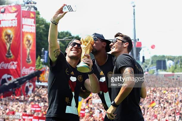 Lukas Podolski Jerome Boateng and Mesut Oezil celebrate on stage at the German team victory ceremony on July 15 2014 in Berlin Germany Germany won...