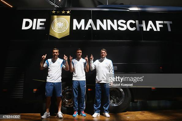 Lukas Podolski Jonas Hector and Bastian Schweinsteiger of Germany present the new team bus of Germany from Mercedes during a press conference ahead...