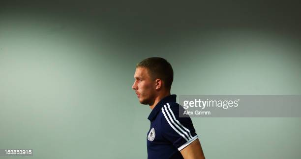 Lukas Podolski leaves a Germany press conference ahead of their FIFA 2014 World Cup group C qualifying match against Ireland at CommerzbankArena on...