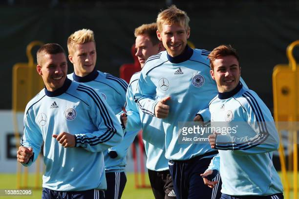 Lukas Podolski Marco Reus MarcAndre ter Stegen Per Mertesacker and Mario Goetze warm up during a Germany training session ahead of their FIFA 2014...