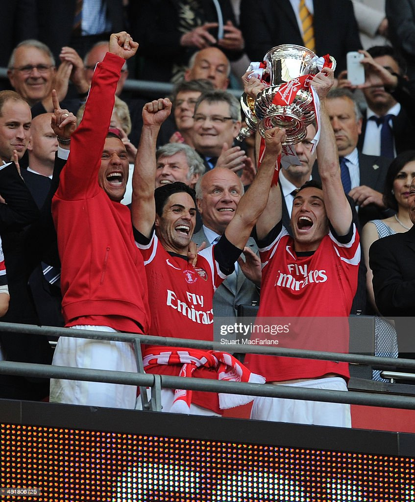 Lukas Podolski, Mikel Arteta and Thomas Vermaelen lift the FA Cup after the FA Cup Final between Arsenal and Hull City at Wembley Stadium on May 17, 2014 in London, England.