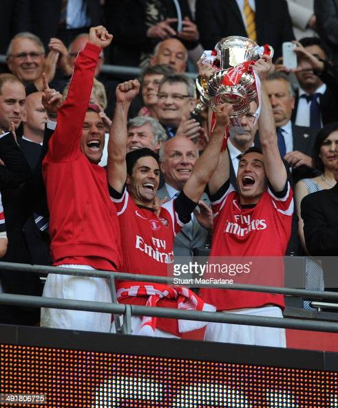 Lukas Podolski Mikel Arteta and Thomas Vermaelen lift the FA Cup after the FA Cup Final between Arsenal and Hull City at Wembley Stadium on May 17...