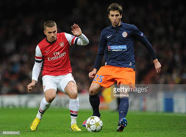 Lukas Podolski of Arsenal and Mathieu Deplagne of Montpellier Herault SC during the UEFA Champions League Group B match between Arsenal and...
