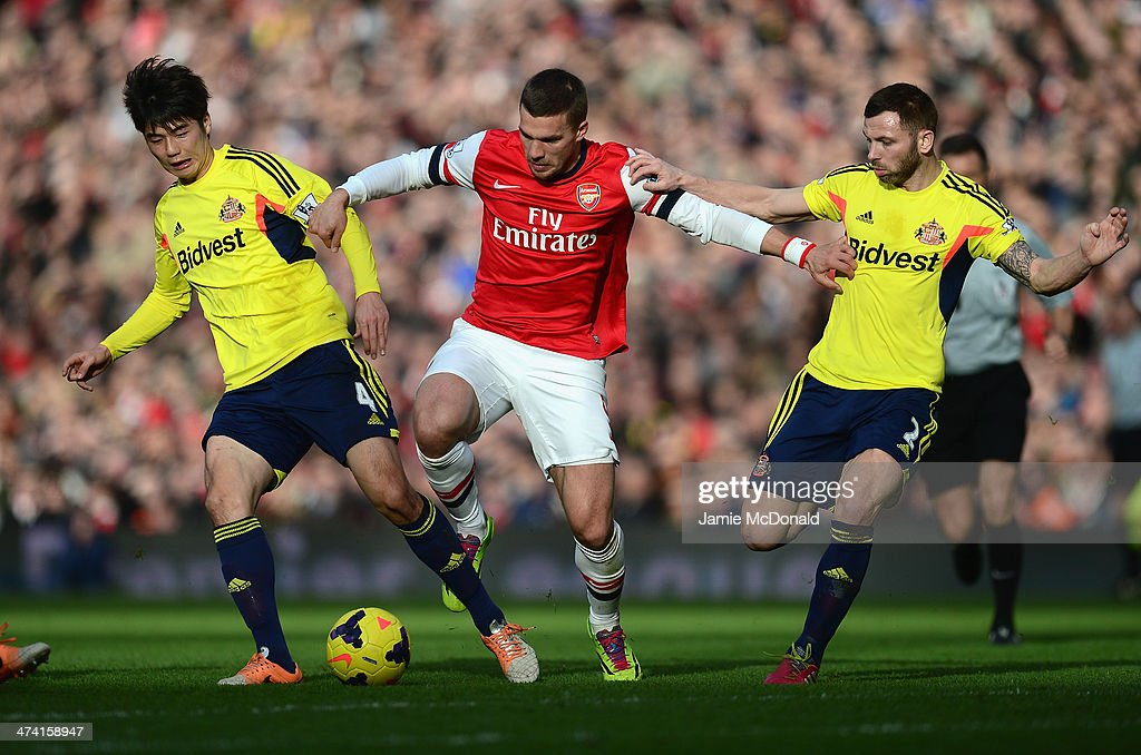 <a gi-track='captionPersonalityLinkClicked' href=/galleries/search?phrase=Lukas+Podolski&family=editorial&specificpeople=204460 ng-click='$event.stopPropagation()'>Lukas Podolski</a> of Arsenal battles with Ki Sung-Yueng and Phil Bardsley of Sunderland during the Barclays Premier League match between Arsenal and Sunderland at Emirates Stadium on February 22, 2014 in London, England.