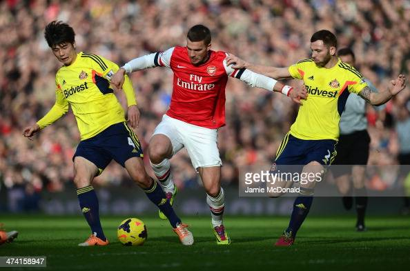 Lukas Podolski of Arsenal battles with Ki SungYueng and Phil Bardsley of Sunderland during the Barclays Premier League match between Arsenal and...