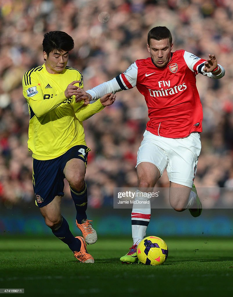 Lukas Podolski of Arsenal battles with Ki Sung-Yueng and Phil Bardsley of Sunderland during the Barclays Premier League match between Arsenal and Sunderland at Emirates Stadium on February 22, 2014 in London, England.