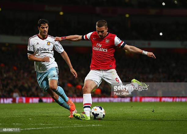 Lukas Podolski of Arsenal beats James Tomkins of West Ham United as he scores their third goal during the Barclays Premier League match between...
