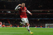 Lukas Podolski of Arsenal celebrates after scoring their second goal during the UEFA Champions League Group B match between Arsenal FC and...