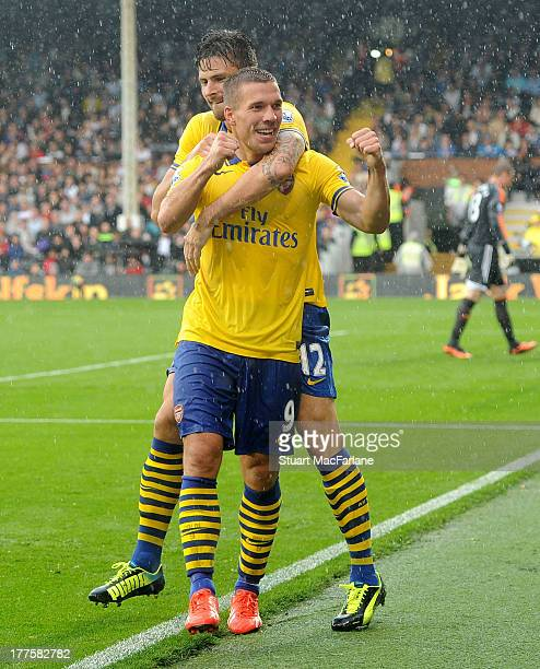 Lukas Podolski of Arsenal celebrates scoring the 3rd goal with Olivier Giroud during the Barclays Premier League match between Fulham and Arsenal at...