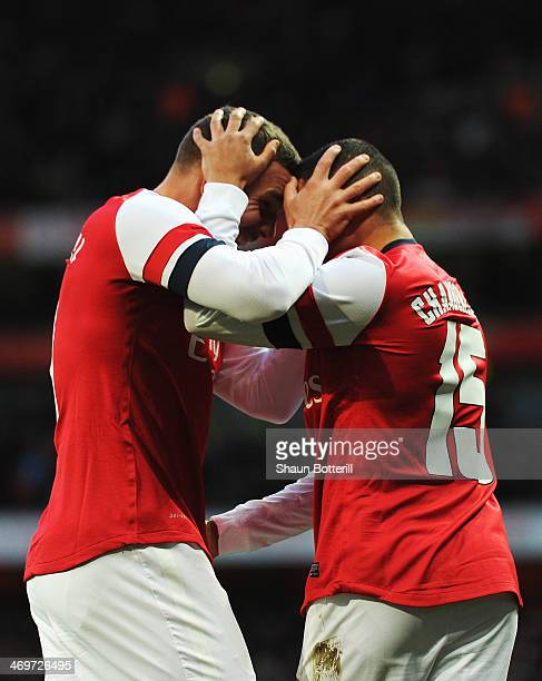 Lukas Podolski of Arsenal celebrates scoring with team mate Alex OxladeChamberlain during the FA Cup Fifth Round match between Arsenal and Liverpool...