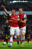 Lukas Podolski of Arsenal celebrates with team mate Per Mertesacker after scoring during the Barclays Premier League match between Arsenal and Wigan...