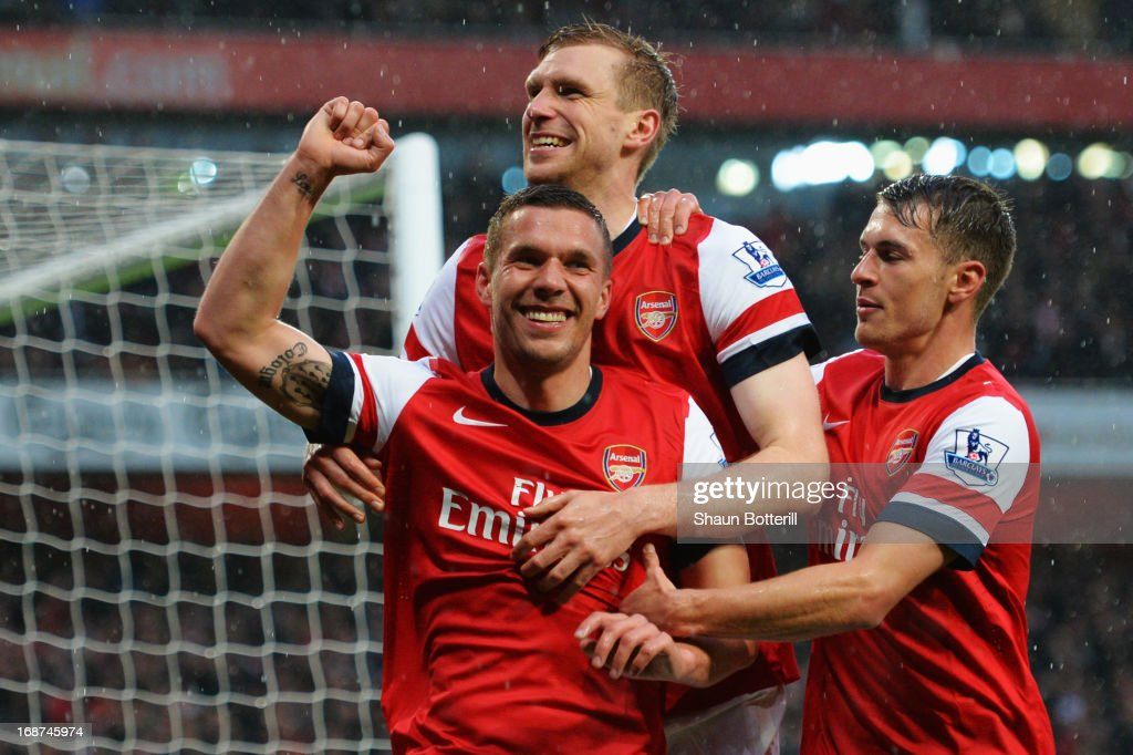 Lukas Podolski (L) of Arsenal celebrates with team mate Per Mertesacker (C) and Aaron Ramsey (R) after scoring during the Barclays Premier League match between Arsenal and Wigan Athletic at Emirates Stadium on May 14, 2013 in London, England.
