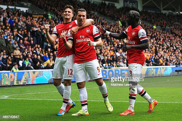 Lukas Podolski of Arsenal celebrates with team mates Olivier Giroud and Bacary Sagna after scoring his sides third goal during the Barclays Premier...