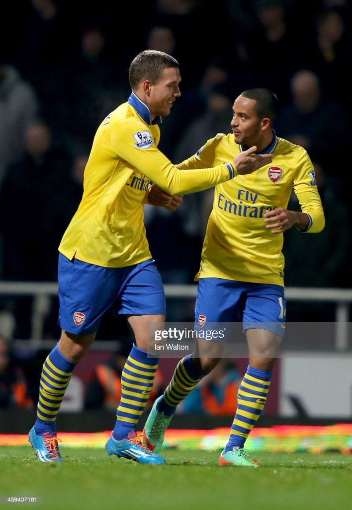 Lukas Podolski of Arsenal (L) celebrates with Theo Walcott as he scores their third goal during the Barclays Premier League match between West Ham United and Arsenal at Boleyn Ground on December 26, 2013 in London, England.