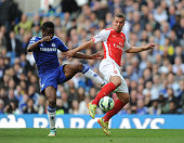 Lukas Podolski of Arsenal challenged by John Mikel Obi of Chelsea during the Barclays Premier League match between Chelsea and Arsenal at Stamford...