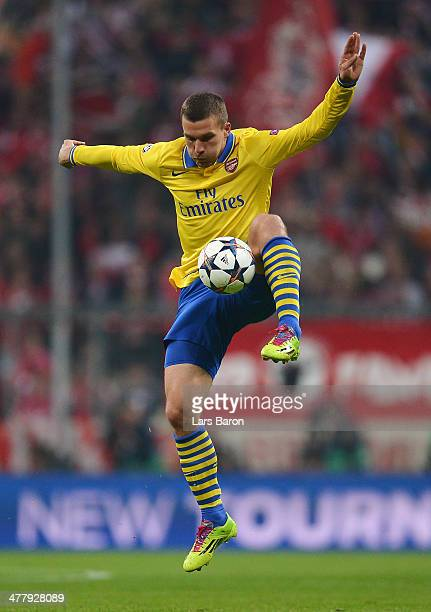 Lukas Podolski of Arsenal controls the ball during the UEFA Champions League round of 16 second leg match between Bayern Muenchen and Arsenal at...