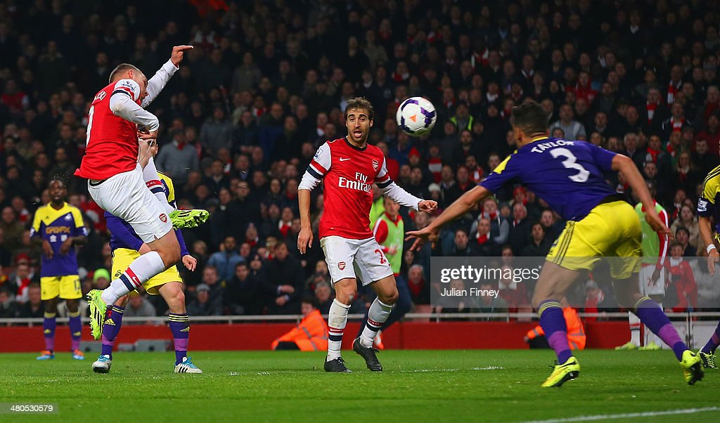 Lukas Podolski of Arsenal scores their first goal during the Barclays Premier League match between Arsenal and Swansea City at Emirates Stadium on March 25, 2014 in London, England.