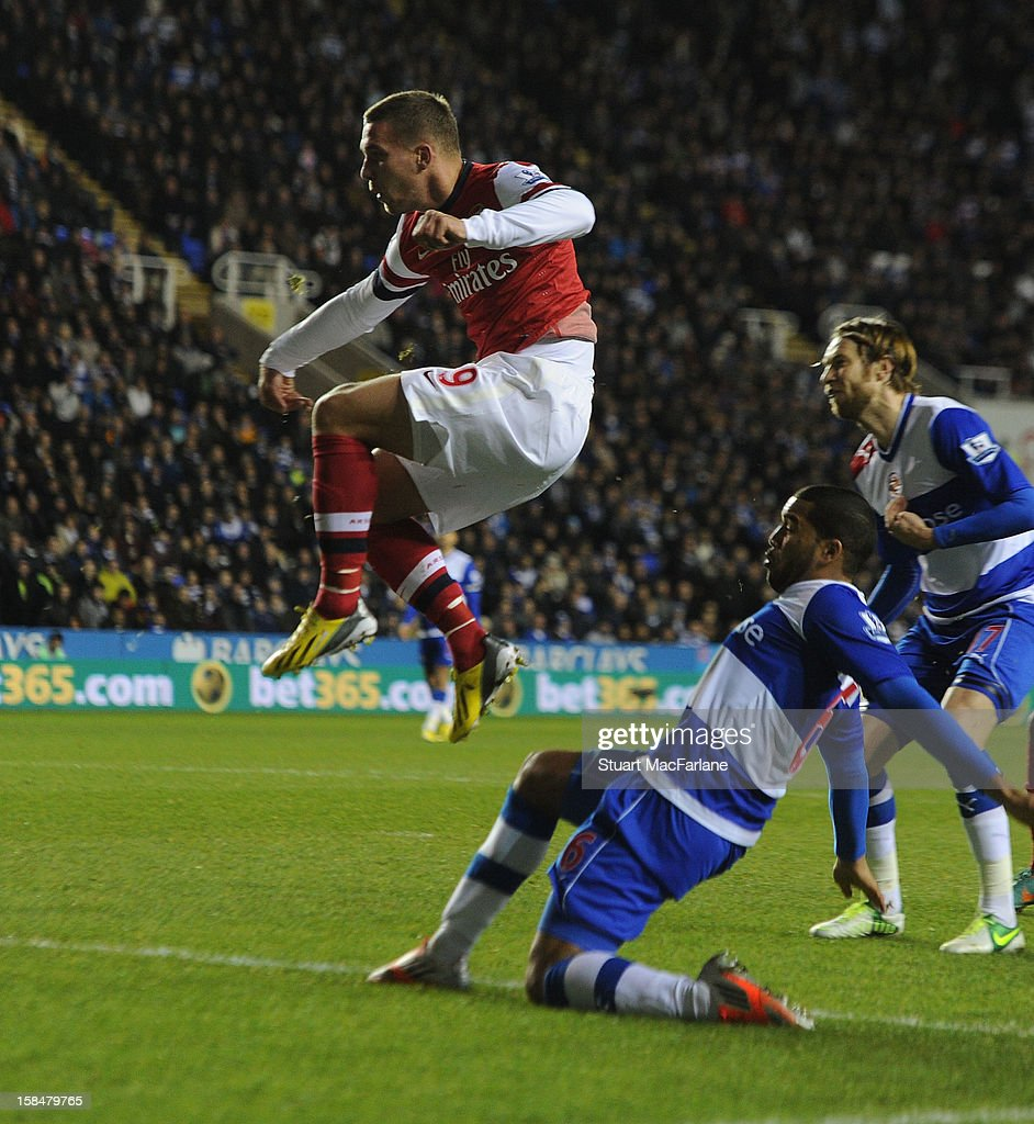 Lukas Podolski (L) of Arsenal shoots past Reading goalkeeper Adam Federici to score the first Arsenal goal during the Barclays Premier League match between Reading and Arsenal at Madejski Stadium on December 17, 2012 in Reading, England.