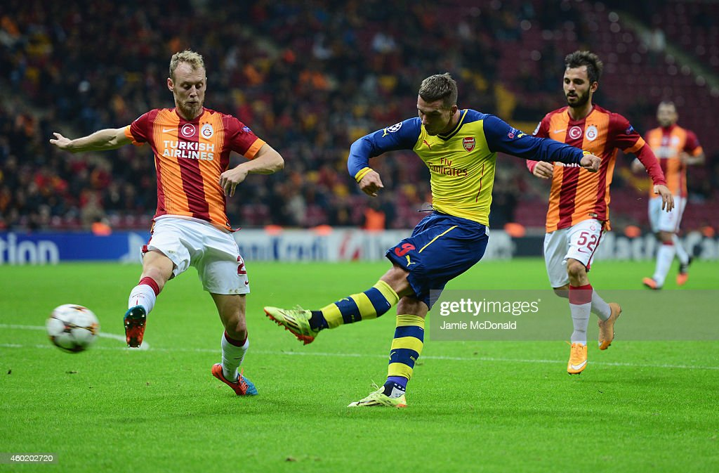 Lukas Podolski of Arsenal shoots past Semih Kaya of Galatasaray during the UEFA Champions League Group D match between Galatasaray AS and Arsenal FC at Ali Sami Yen Arena on December 9, 2014 in Istanbul, Turkey.