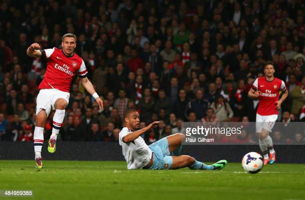 Lukas Podolski of Arsenal shoots past Winston Reid of West Ham United to score their first goal during the Barclays Premier League match between...