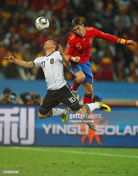 Lukas Podolski of Germany and Sergio Ramos of Spain go up for the ball during the 2010 FIFA World Cup South Africa Semi Final match between Germany...