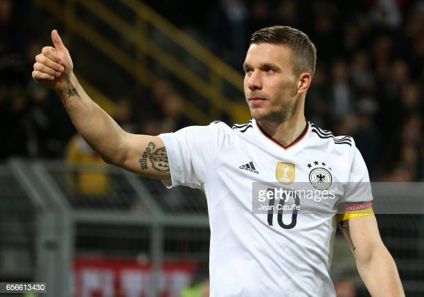 Lukas Podolski of Germany celebrates his last match with the national team with the supporters following the international friendly match between...