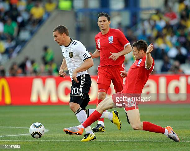 Lukas Podolski of Germany challenged by James Milner of England during the 2010 FIFA World Cup South Africa Round of Sixteen match between Germany...