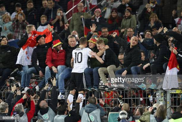 Lukas Podolski of Germany embraces members of the German fans after he played his last international match for the German national team after the...