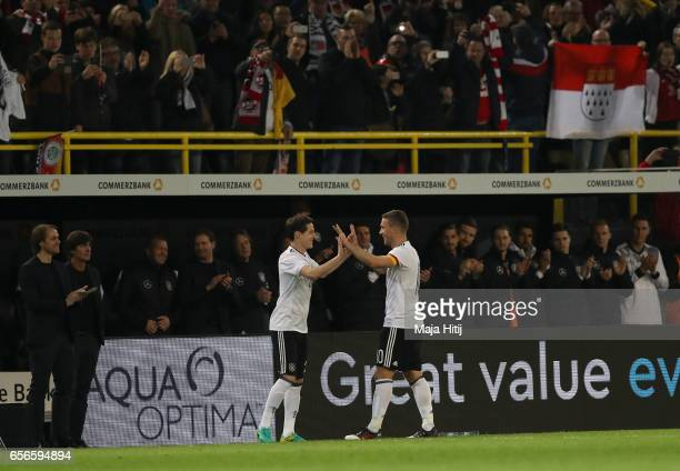 Lukas Podolski of Germany embraces Sebastian Rudy of Germany as he is subbed during his last international match for Germany during the international...
