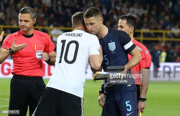 Lukas Podolski of Germany greets captain of England Gary Cahill before the international friendly match between Germany and England at Signal Iduna...