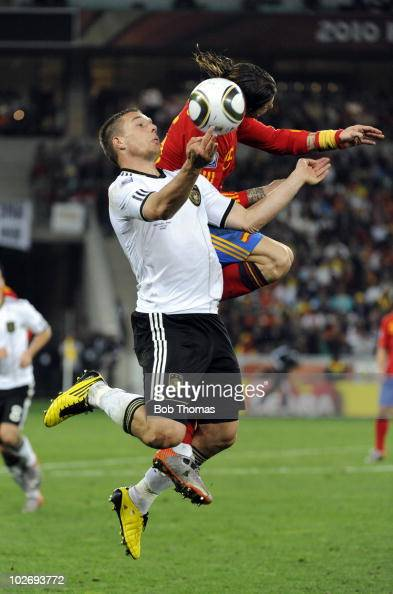 Lukas Podolski of Germany heads the ball with Sergio Ramos of Spain during the 2010 FIFA World Cup South Africa Semi Final match between Germany and...