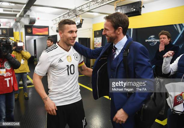 Lukas Podolski of Germany is congratulated by England manager Gareth Southgate after playing his last game for Germany in the international friendly...