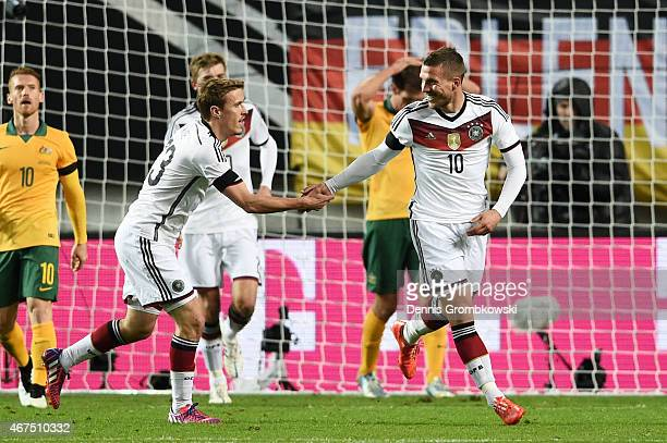 Lukas Podolski of Germany is congratulated by teammate Max Kruse of Germany after scoring his team's second goal during the International Friendly...
