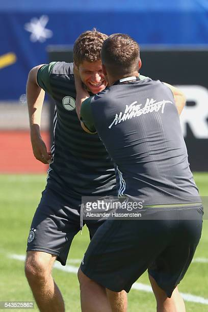 Lukas Podolski of Germany jokes with his team mate Thomas Mueller during a Germany training session at Ermitage Evian on June 29 2016 in...
