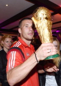 Lukas Podolski of Germany poses with the World Cup trophy as he celebrates with teammates at a party after winning the 2014 FIFA World Cup Brazil...