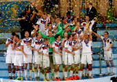 Lukas Podolski of Germany raises the World Cup trophy in celebration with his teammates after defeating Argentina 10 in extra time during the 2014...