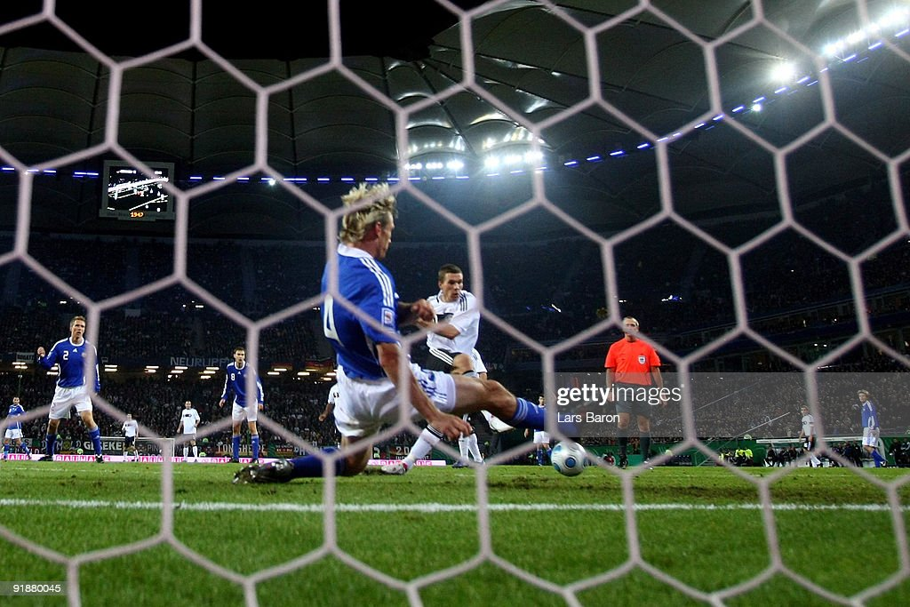 Lukas Podolski of Germany scores his team's first goal against Sami Hyypiae of Finland during the FIFA 2010 World Cup Group 4 Qualifier match between...