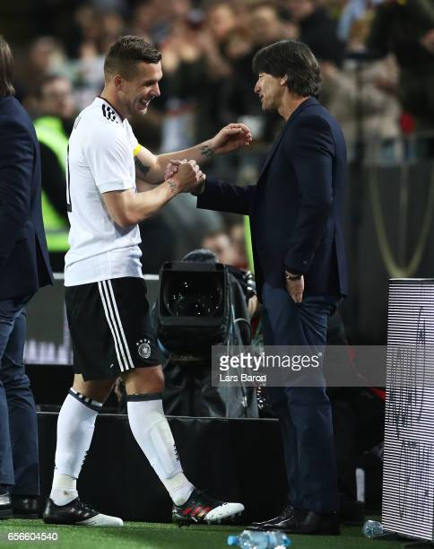 Lukas Podolski of Germany shakes hands with Joachim Loew manager of Germany as he is subbed during his last international match for Germany during...