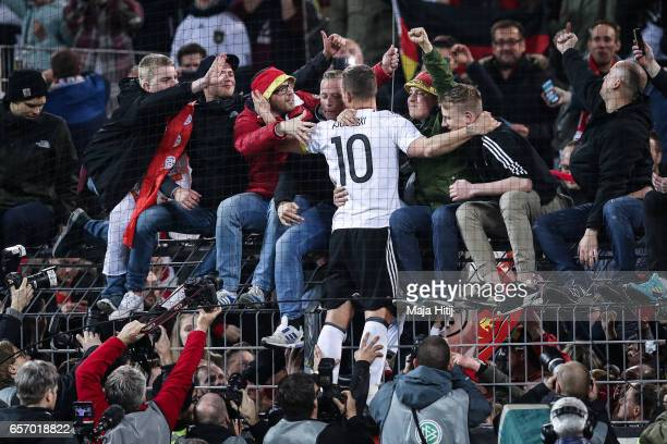 Lukas Podolski of Germany shows appreciation to the fans after his last international match for Germany after the international friendly match...