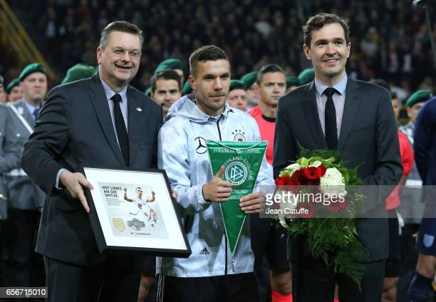 Lukas Podolski of Germany stands between DFB President Reinhard Grindel and Dr Friedrich Curtius prior to his final game for Germany before the...