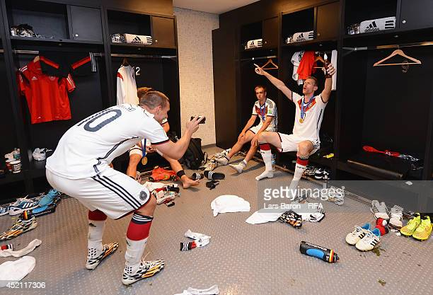 Lukas Podolski of Germany takes a picture of teammate Per Mertesacker of Germany in the Germany dressing room after the 2014 FIFA World Cup Brazil...