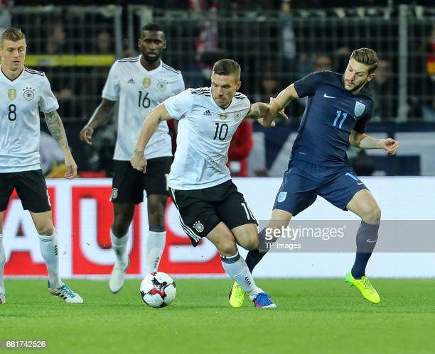 Lukas Podolski of Germany und Adam Lallana of England battle for the ball during the international friendly match between Germany and England at...