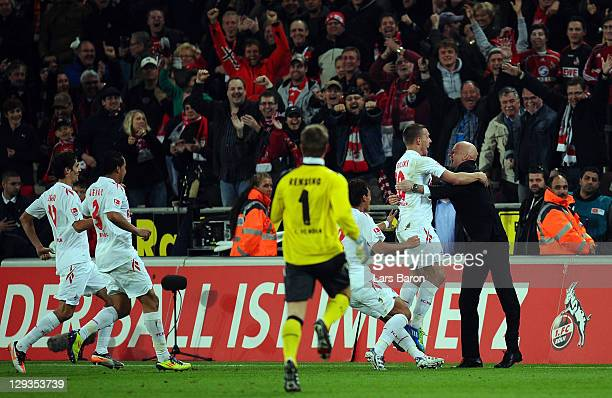Lukas Podolski of Koeln celebrates with head coach Stale Solbakken after scoring his teams second goal during the Bundesliga match between 1 FC Koeln...