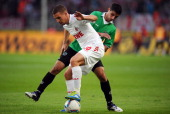 Lukas Podolski of Koeln is challenged by Lars Stindl of Hannover during the Bundesliga match between 1 FC Koeln and Hannover 96 at...