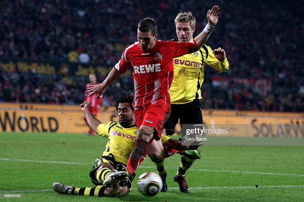 Lukas Podolski of Koeln is challenged by Patrick Owomoyela and Jakub Blaszczykowski of Dortmund during the Bundesliga match between 1 FC Koeln and...