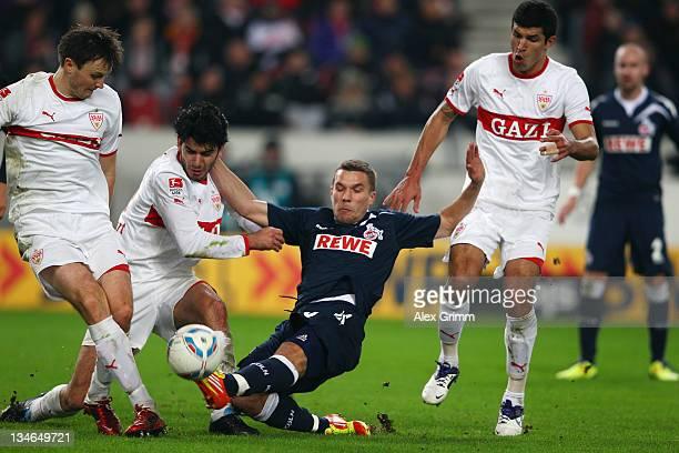 Lukas Podolski of Koeln is challenged by William Kvist Serdar Tasci and Maza of Stuttgart during the Bundesliga match between VfB Stuttgart and 1 FC...